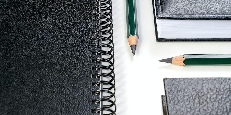 Stifte und Notizheft als Symbolbild für Bewerbung Promotion Doktorand Doktorarbeit
